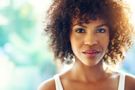 emotionless: Close up portrait of beautiful curly girl looking at camera emotionless. Copyspace