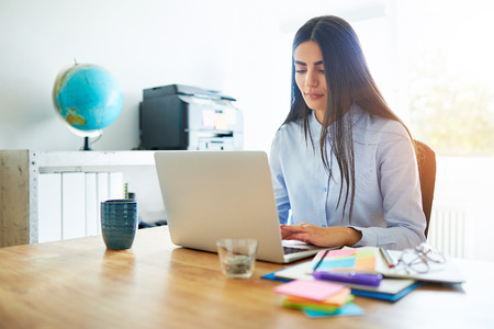 competent: Competent young business secretary working at a laptop at a wooden desk surrounded by colorful memo notes to organise and prioritise her tasks Stock Photo
