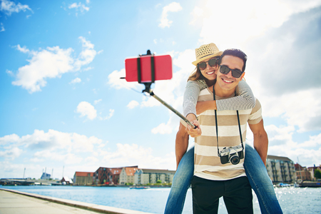 ピギーを取り戻す若い女性と彼らをもたらす棒の grinningas に自分の携帯電話で selfie を取って楽しい愛する若い観光客男、水辺の背景に乗る 写真素材