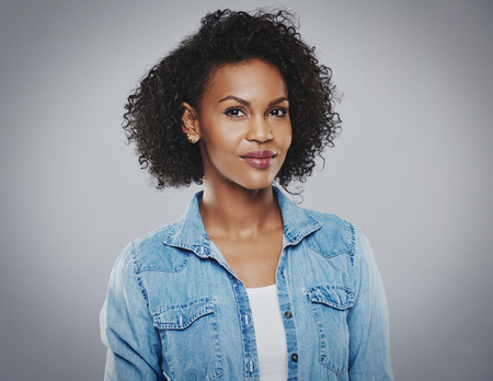 face centered: Confident beautiful black woman with blue jean shirt on gray background Stock Photo