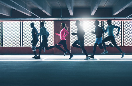 Group of diverse urban runners sprinting across the frame in an indoor car park as they workout backlit by the sun through a grid
