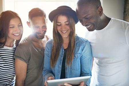 Diverse groep van vier volwassen mannen en vrouwen lachen terwijl staan dicht bij elkaar in de buurt van een tablet-computer