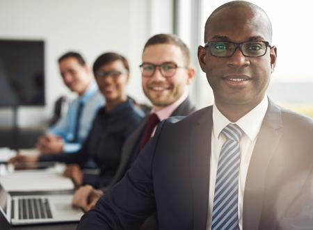 Vriendschappelijke zekere Afrikaanse zakenman in een leidinggevende ontmoeting met een groep van multiraciale collega's lachend naar de camera