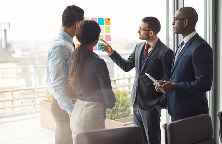 유리에 다채로운 메모 세트를 가리키는 사무실에서 큰 밝은보기 창 앞에 함께 브레인 스토밍 서 Multiracial 비즈니스 팀 스톡 콘텐츠