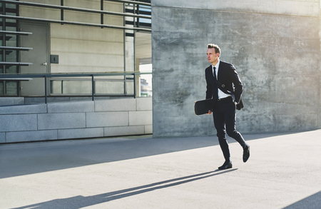 haste: Young businessman in suit holding skateboard at hand and walking in haste down street in sunlight. Stock Photo