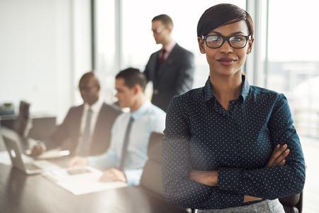 Vertrouwen jonge Afrikaanse zakenvrouw staande met gevouwen armen lachen naar de camera in een directiekamer met mannelijke collega's in de achtergrond