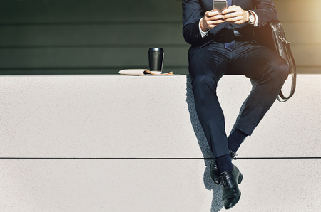 Crop male wearing suit sitting on parapet with cup of coffee near and using phone