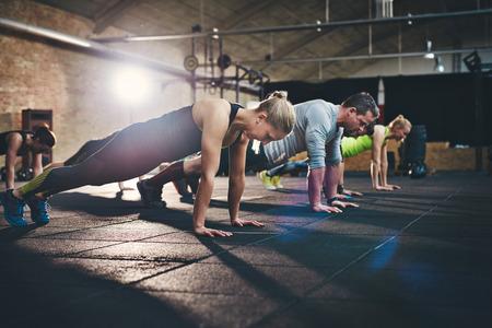 Grupo de adultos hace empuje hacia arriba ejercicios en gimnasio de entrenamiento cruzado de la aptitud física de interior con destello de luz brillante sobre ellas Foto de archivo