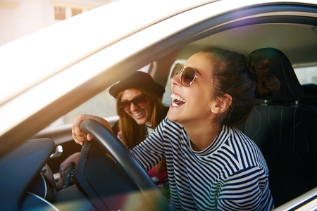 Laughing young woman wearing sunglasses driving a car with her girl friend , close up profile view through the open window 스톡 콘텐츠