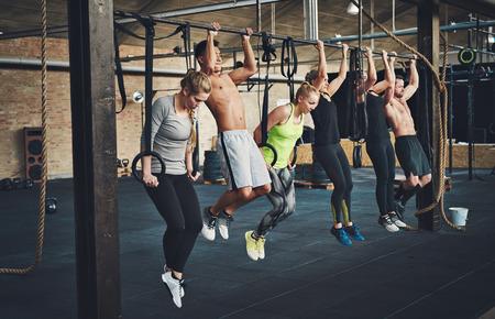 Grupo de seis adultos jóvenes hombres y mujeres atractiva que hace pull ups en la barra transversal en gimnasio de entrenamiento en forma con paredes de ladrillo y esteras negras