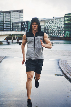 Full length shot of young man running down rainy street and looking at street. Stock Photo