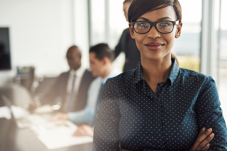 affiliates: Beautiful young grinning professional Black woman in office with eyeglasses, folded arms and confident expression as other workers hold a meeting in background