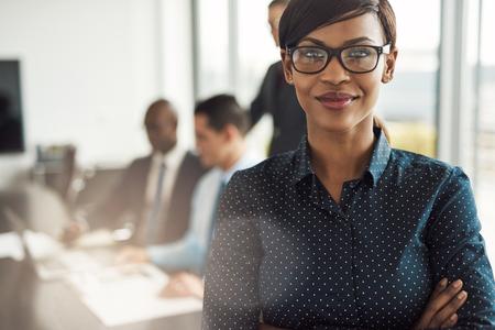 Mooie jonge professionele grijnzende zwarte vrouw in het kantoor met brillen, gevouwen armen en vertrouwen expressie als andere werknemers een bijeenkomst in de achtergrond te houden Stockfoto