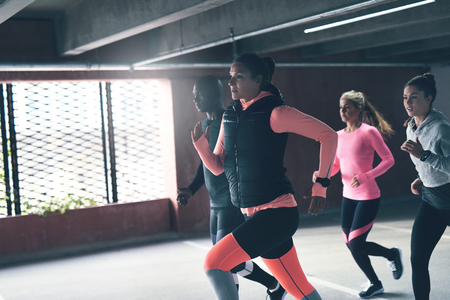 close out: Close up view of runners working out indoors over big window. Copyspace Stock Photo