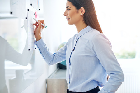 Young businesswoman writing notes on a notice or document pinned up on a reflective board in a close up upper body cropped view