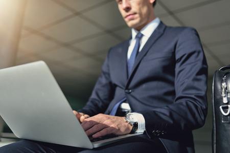 and the horizontal man: Serious man working on a laptop. Horizontal outdoors shot.