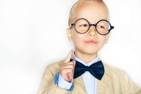 Jongetje in formele pak en een bril met een trots gezicht houden vinger op een witte achtergrond.