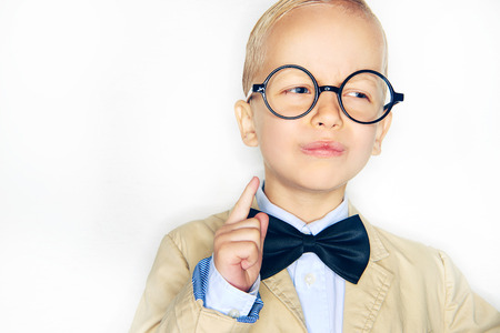 Little boy in formal suit and glasses with proud face holding finger up on white background.