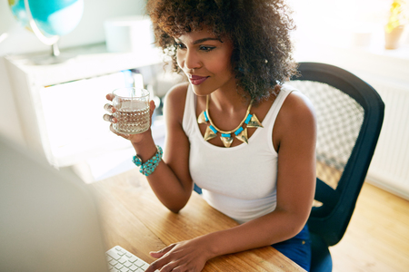 View of attractive brunette woman holding glass of water while working at computer in office.