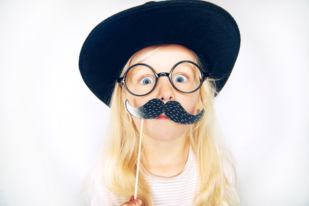 girl in a hat: Little girl wearing black hat and glasses holding fake moustache on stick and looking at camera.