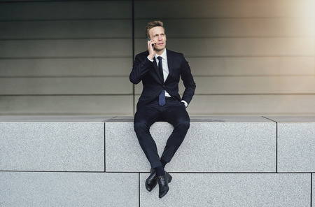 and the horizontal man: Confident man speaks smartphone with legs crossed. Horizontal outdoors shot