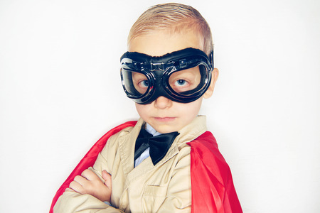 confidently: Little boy wearing aviator glasses and red cloak looking confidently at camera on studio background.
