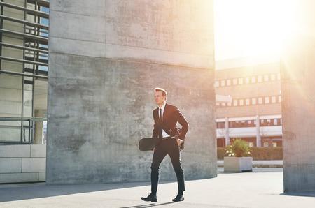 office man: Walking businessman holding a skateboard. Horizontal outdoors shot Stock Photo