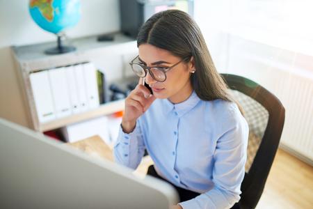 黒い長い髪と彼女の後ろの棚の上の地球と小規模オフィスで電話で眼鏡で深刻な女性