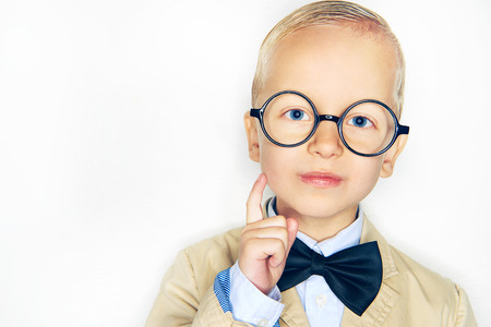 Prodigy: Little boy in glasses and suit touching face with finger and looking at camera on studio background.