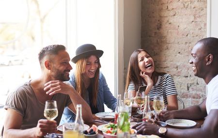 Groep jonge vrienden met plezier en lachen tijdens een diner aan tafel in een restaurant.