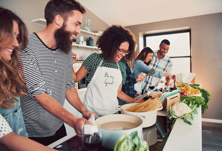 Large group of six happy friends preparing food for a pasta cooking class at table at home or in a small culinary school Stock Photo
