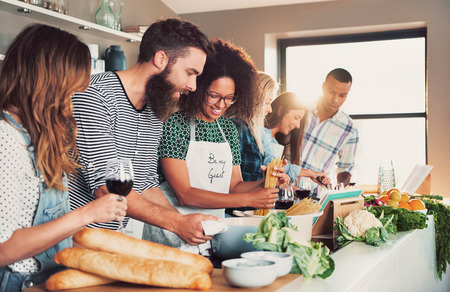 tasteful: Multiracial funny friends cook some tasteful food at kitchen while drinking wine. Stock Photo