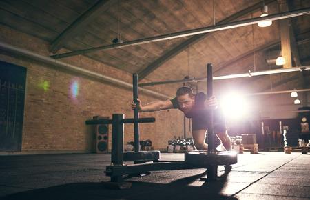 Strong man doing push-ups from metal bogie. Horizontal indoors shot Stock Photo