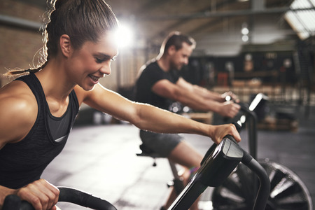 女性は満足ですか? 男とサイクリング マシンに乗ってトレーナーの後ろにぼかしでスポーツウェア。