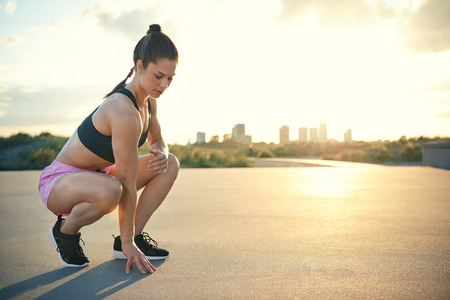 Young woman with athletic toned body squatting near ground outside during early morning as sun reaches over buildings and background Stock Photo