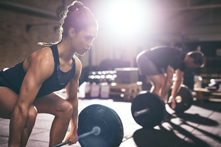 Sportive woman and man lifting a dumbbell from squats in light gym. Stockfoto