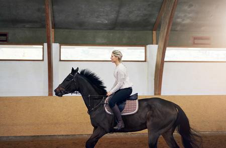 saddler: Profile shot of a woman riding a black horse