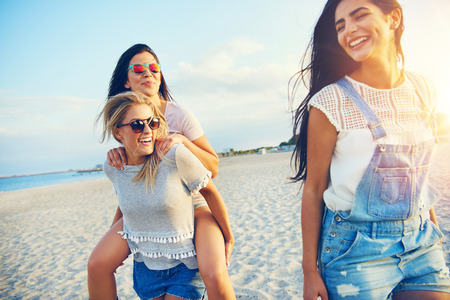 travel background: Young smiley girl carrying her friend piggyback while three female friends in sunglasses walking on beach.