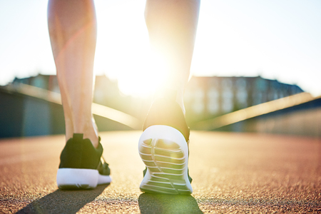 low angle view: Athlete preparing to run down empty road on a bright day as seen from low angle view