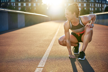 Athletic woman prepares to run as she kneels on empty jogging path as she is highlighted by the sun Stock Photo