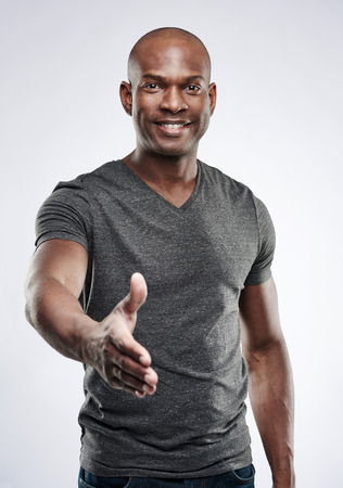 black: Single handsome young Black male fitness trainer in gray compression shirt reaching out toward camera to shake hands over neutral background