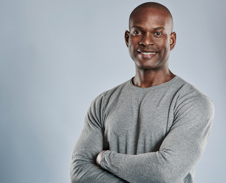 contented: Single handsome black man with folded arms, cheerful expression and pleasant smile in gray compression shirt over neutral background with copy space