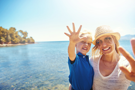 Cute little boy waving at the camera on a beach as she is held in his smiling mothers arms against a backdrop of the ocean Stock Photo