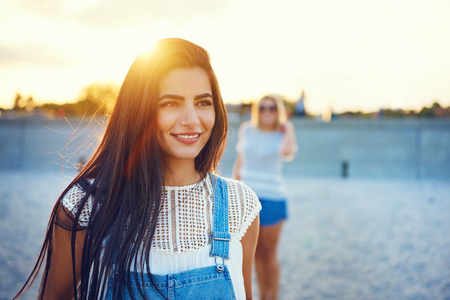 Beautiful young grinning woman in long hair and blue jeans overalls with friend out of focus behind her