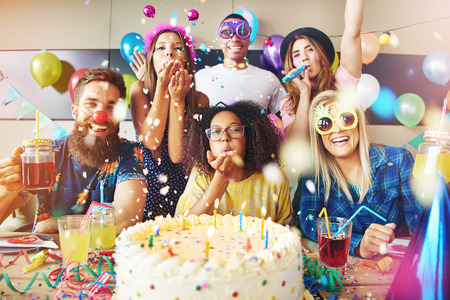 Confetti flying around group of cheerful friends celebrating a party with large cake and drinks on table in foreground Stock Photo