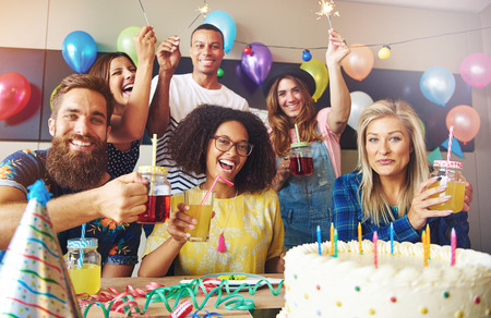 Group of six friends holding drinks at birthday celebration in room filled with colorful balloons