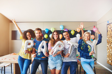 merrymaking: Celebrating friends holding PARTY balloons while raising their hands in celebration Stock Photo