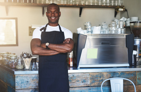 mani incrociate: Young smiling black male in apron posing with hands crossed and looking at camera near stand.