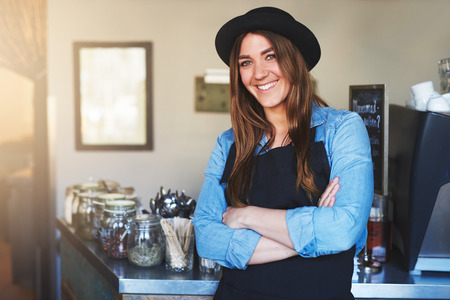 mani incrociate: Pretty girl in black hat and apron posing with hands crossed and smiling at camera in cafe. Archivio Fotografico