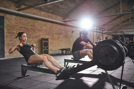 Young athletic adults in sportswear training on body-builders in gym.